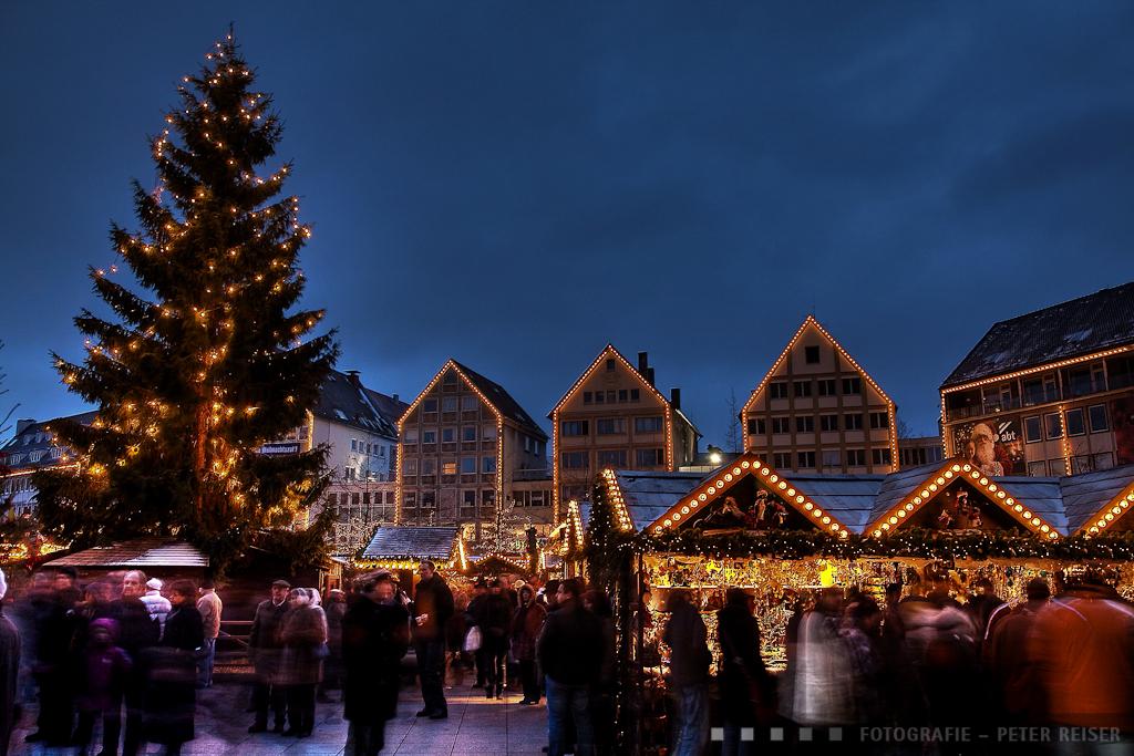 Ulmer Weihnachtsmarkt mit Weihnachtsbaum und Marktbesuchern in den Marktgassen